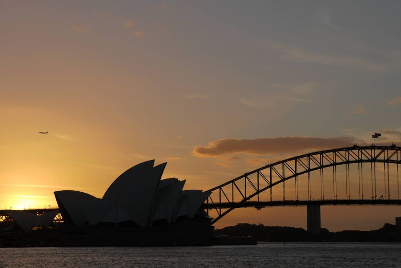 The sun setting over Sydney Opera House and Sydney Harbor Bridge