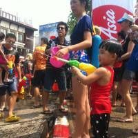 Thai Boy Squirting a Water Pistol During Songkran 2014