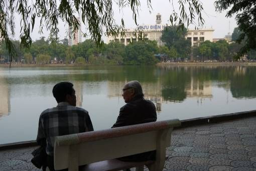 People Sitting by Hoan Kiem Lake in Vietnam