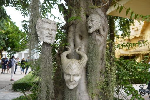 Heads of move characters hanging from trees at the White Temple in Thailand