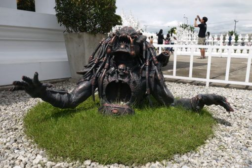 Predator statue rising from the ground at the White Temple