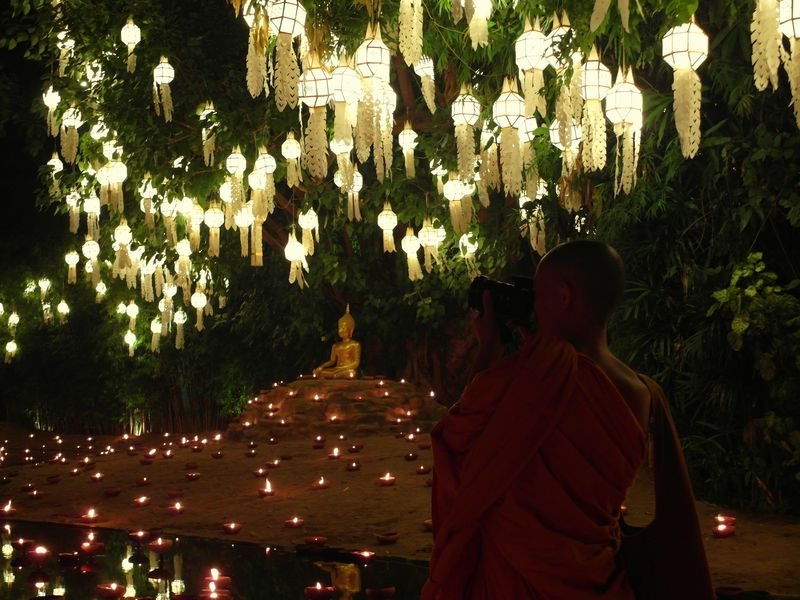Monk taking photos of a lantern display at Wat Phan Tao during Yi Peng, Chiang Mai