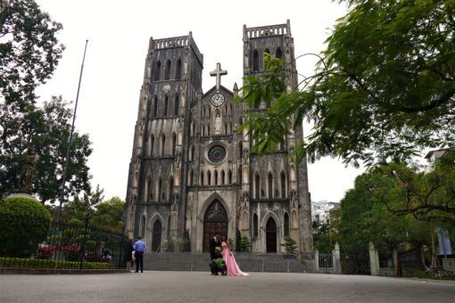 Newlyweds posing for photos outside St Joseph's Cathedral, Hanoi