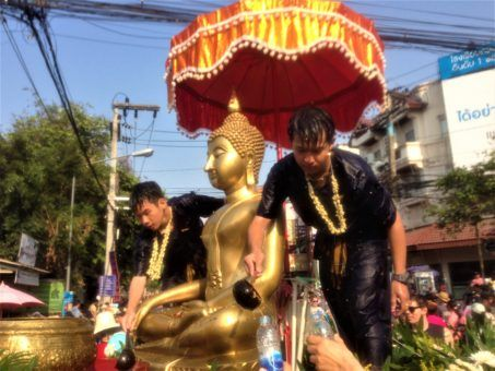 Buddhists blessing the Buddha statues for Songkran festival in Thailand