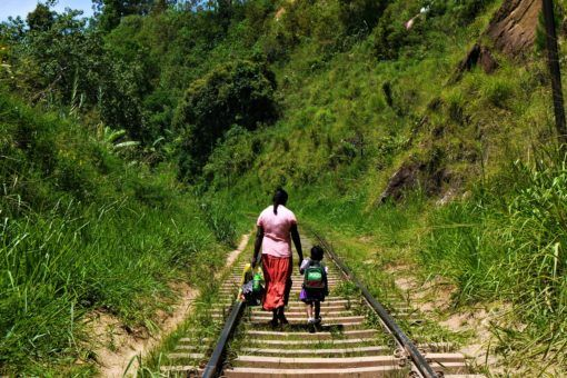 Mother and child walking on the Sri Lanka railway tracks