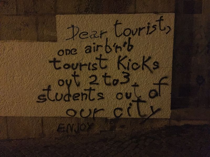 Painted sign in Coimbra complaining about tourists using Airbnb