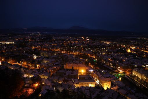 Aerial view of Ljubljana's snow-covered rooftops at night