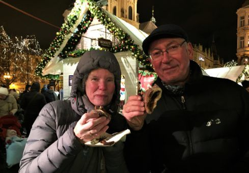 Andrew's mum and dad eating the trdelnik at the Prague Christmas Market