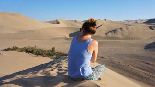 Looking at the view of Desert sand dunes in Huacachina, Peru