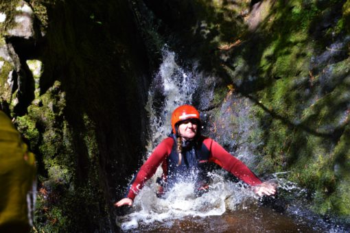 Sliding down a water chute on a canyoning trip with ACE Adventures, Scotland